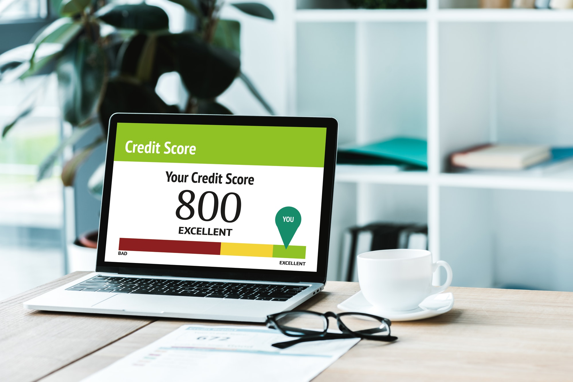 cup of coffee near laptop with credit score lettering and numbers on screen