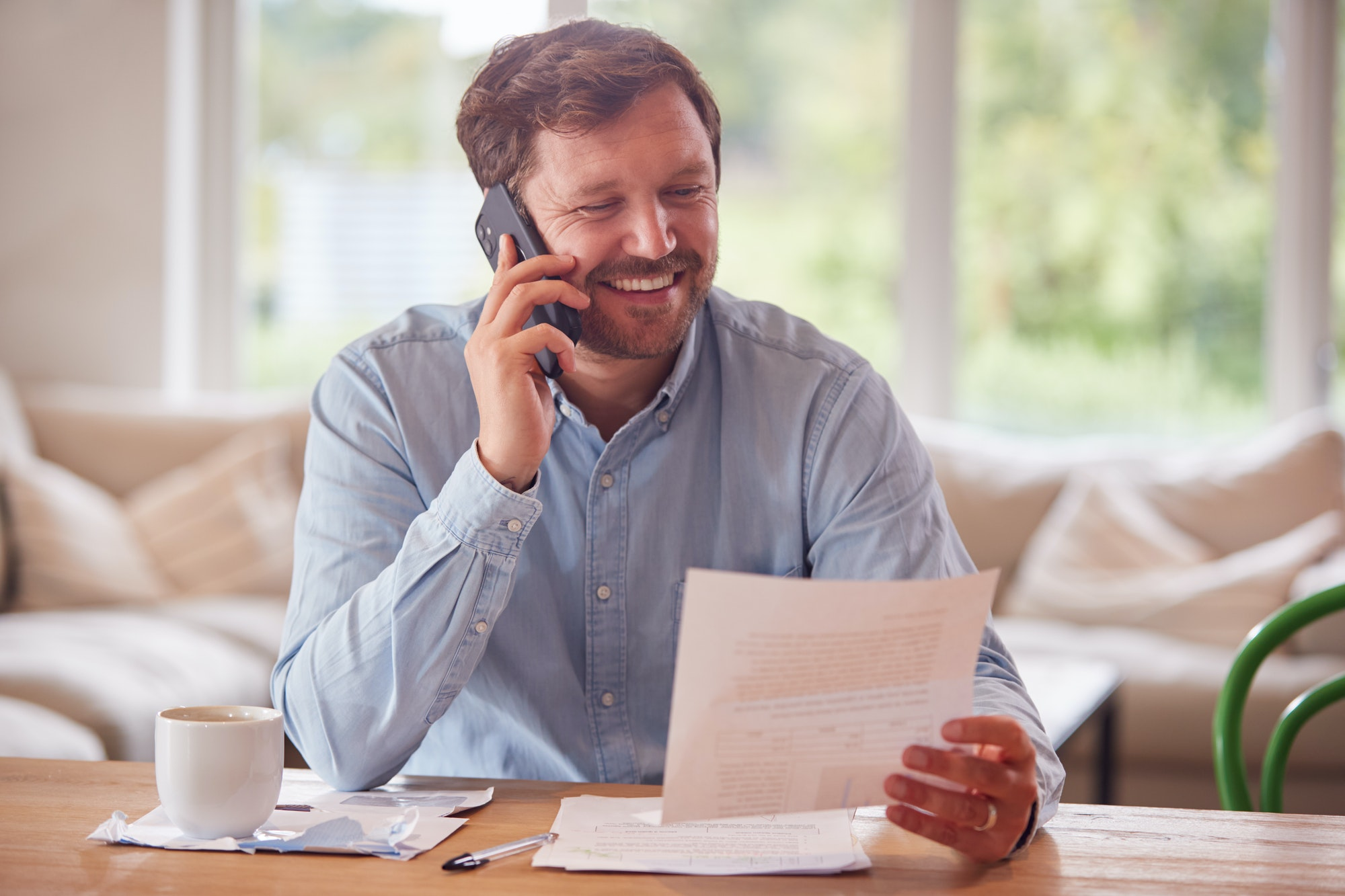 Smiling Man On Phone Call Sitting At Table At Home Reviewing Domestic Finances
